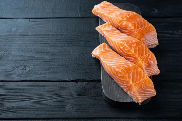 Portion set of salmon fillet, on black wooden table