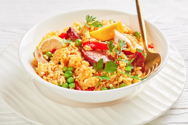 Portion of spanish chicken paella with valencian bomba rice, chicken thigh meat, chorizo sausages, vegetables and spices served on a white plate on a white wooden table, close-up