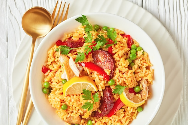 Portion of spanish chicken paella with valencian bomba rice, chicken thigh meat, chorizo sausages, vegetables and spices served on a white plate on a white wooden table, flat lay,macro