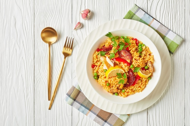 Portion of spanish chicken paella with valencian bomba rice, chicken thigh meat, chorizo sausages, vegetables and spices served on a white plate on a white wooden table, flat lay