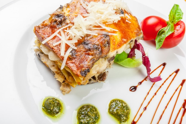 Portion of tasty lasagna, isolated on white