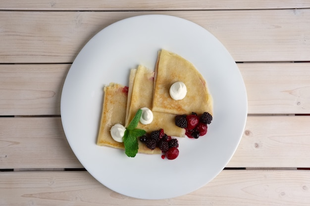 Portion on thin pancakes with sweet cream cheese and berries. top view.
