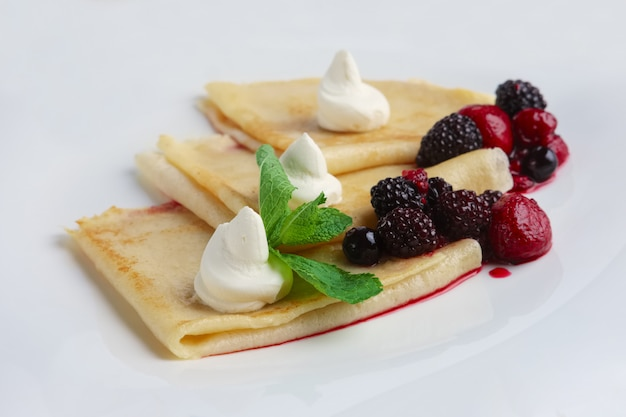Portion on thin pancakes with sweet cream cheese and berries.
