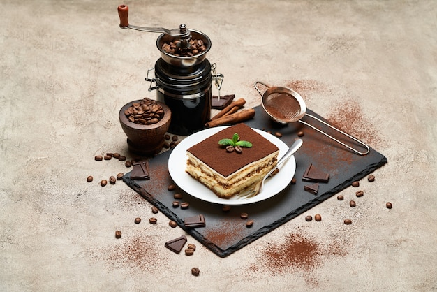 Portion of traditional italian tiramisu dessert and hand coffee grinder on grey concrete table