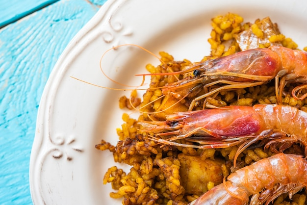 Portion of typical spanish paella with rice and seafood with three prawns on top blue background
