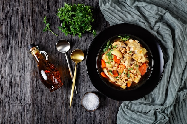 A portion of white bean, vegetables and pork steak stew in a black bowl on a dark wooden table, horizontal view from above, flat lay, free space