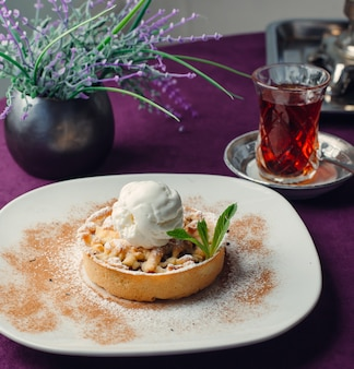 Portioned apple tarte with vanilla ice cream, on purple tablecloth