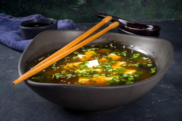 Порционный мисо-суп с водорослями вакаме, тофу и палочками для еды на черном фоне