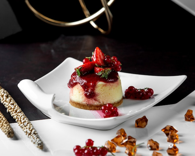Portioned cheesecake topped with berries and jam