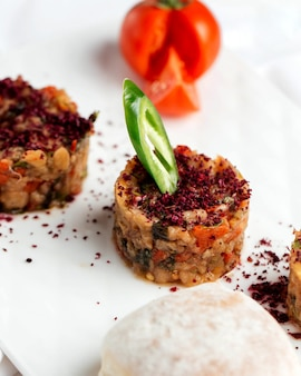 Portioned smoked aubergine salad garnished with sumac and pepper