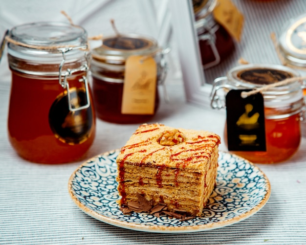 Portioned square honey cake garnished with syrup and walnut