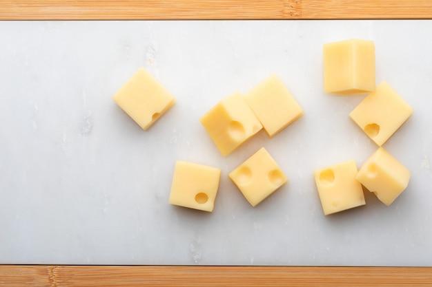 Порции (кубики, кубики) швейцарского сыра эмменталь. текстура отверстий и альвеол. на белом мраморном столе.