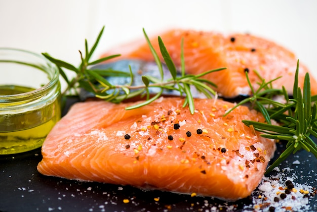 Portions of fresh raw salmon fillets with aromatic herbs and olive oil