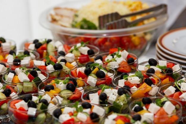 Порции салатов греческий и цезарь на столе. питание для мероприятий, торжеств и деловых встреч.