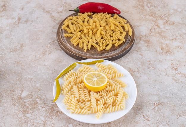 Порции макаронных изделий в сыром и приготовленном состоянии на мраморной поверхности.