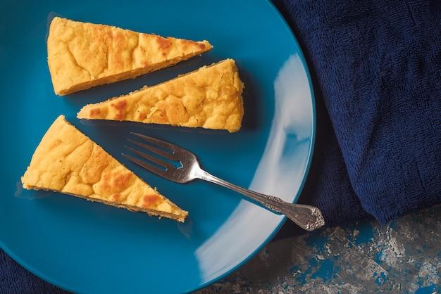 Порции тыквенного пирога и прибрежного сыра на красивой голубой тарелке