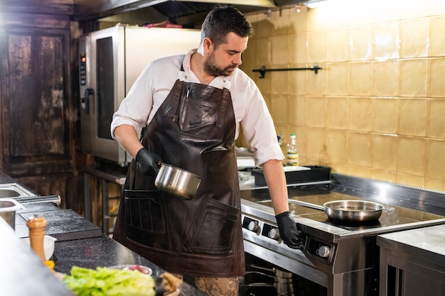 業務用厨房でストーブの温度をオンにしながらストーブの温度を選択する革のエプロンのかっこいいシェフ