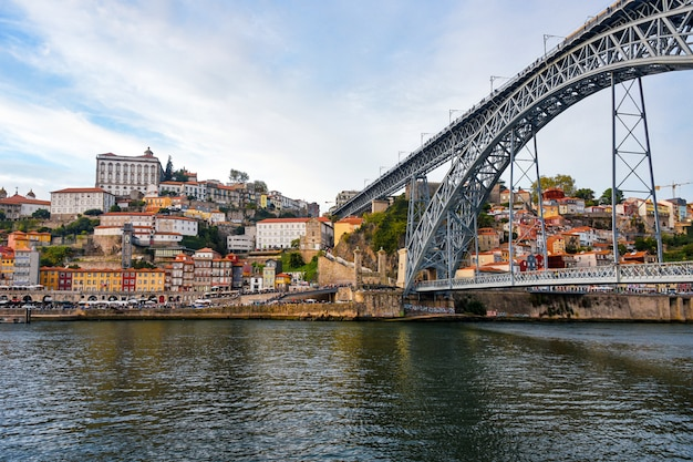 Порту, район рибейра, португалия старый город рибейра вид с разноцветными домами и мост луиса i - металлический арочный мост через реку дору. символ города и самая популярная туристическая достопримечательность