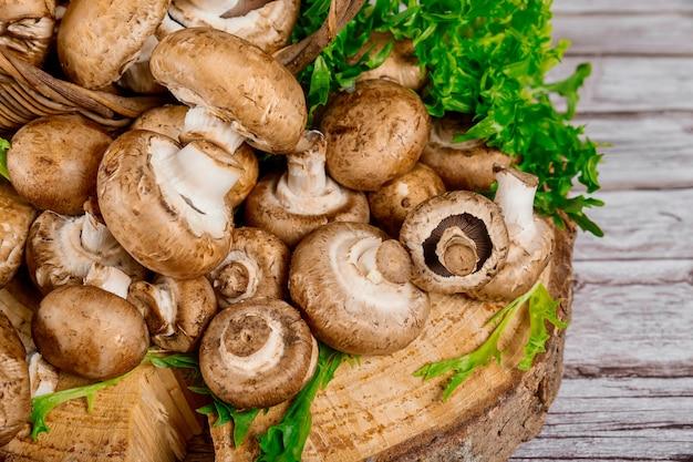 Шампиньоны грибов портобелло коричневые на деревянном столе.