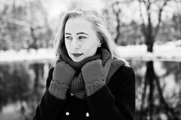 Portrai of blonde girl in red scarf and coat against frozen lake on winter day.