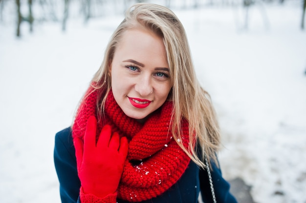 Portrai of blonde girl in red scarf and coat on winter day.