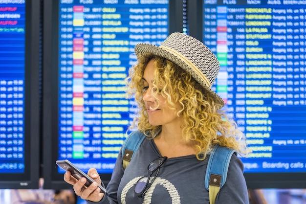 美しい大人の白人女性のportraiは、スマートフォンでアプリを旅行してチェックし、空港のディスプレイを出発して、表面技術とインターネット接続の現代人の時間とともに表示します