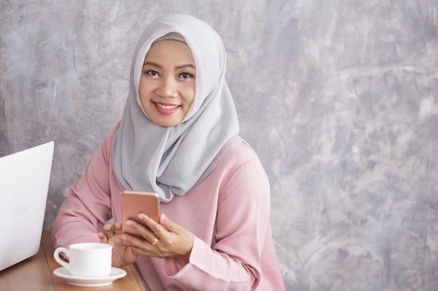 コピースペース付きの携帯電話を持って笑っている美しいイスラム教徒の女性の肖像画