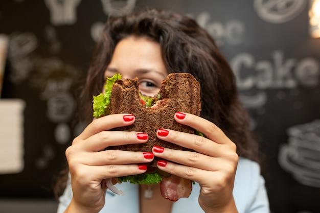 Portrai of young caucasian brunette woman looking through bitten sandwich