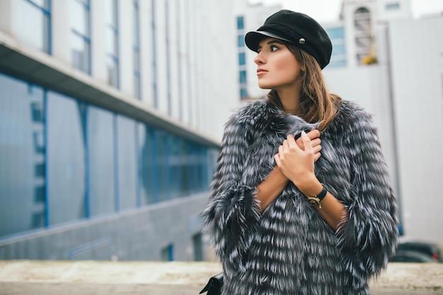 Portrair of fashionable woman walking in city in warm fur coat wearing black cap