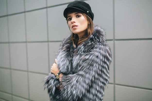 Portrair of fashionable woman walking in city in warm fur coat, winter season, cold weather, wearing black cap, street fashion trend
