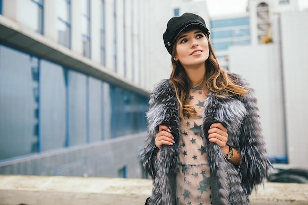 Портрет модной женщины, гуляющей по городу в теплой шубе и черной кепке
