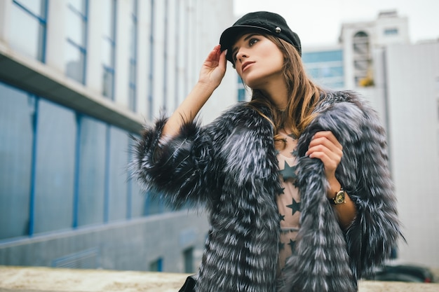 黒い帽子をかぶった暖かい毛皮のコートで街を歩くファッショナブルな女性のportrair