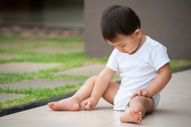 Portrait of 1 year old asian-looking girl playing alone in the yard. outdoor scene. copy space