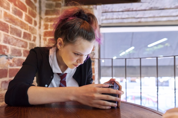 Portrait of 15 years old teenage girl in school uniform with tie sitting on chair looking at camera crane, brick wall background, copy space window