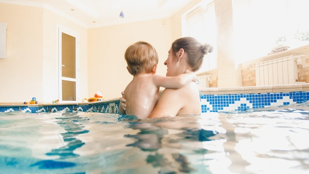 Portrait of 3 years old toddler boy with young mother swimming in the indoors pool. child learning swimming and doing sports. family enjoying and having fun in water