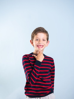 Portrait of a 7 year old boy pointing at his front missing tooth, isolated on gray background
