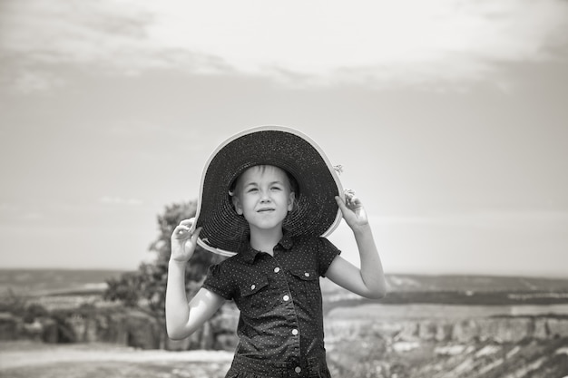 The portrait of 8 years old girl in the big hat.
