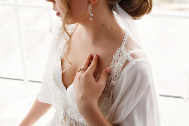 세로 큰 창 근처 속옷에 섹시 한 금발 신부. 세련 된 화이트 인테리어와 호텔 방에서 아름 다운 신부의 아침. 흰 속옷이나 잠옷에 젊은 여자의 얼굴을 닫습니다