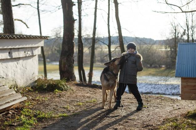 Портрет улыбающегося мальчика, гуляющего с большой собакой породы немецкая овчарка.