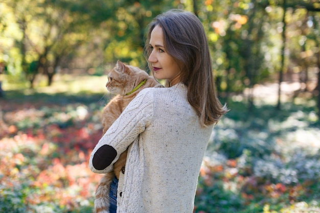 自然の幸せな女の子とかわいいふわふわ猫屋外で大きな赤いふわふわ猫を保持している女性の肖像画