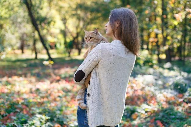 自然の笑顔の女性と散歩で彼女の素敵なペットに大きな赤いふわふわの猫を保持している女性の肖像画