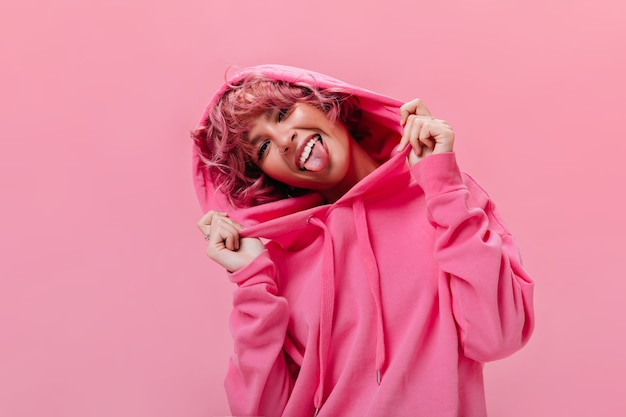 Portrait of active cheerful pink-haired woman in fuchsia oversized hoodie shows tongue and makes funny face on isolated wall