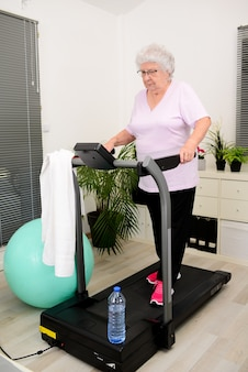 Portrait of an active and dynamic senior woman doing sport fitness at home walking on treadmill