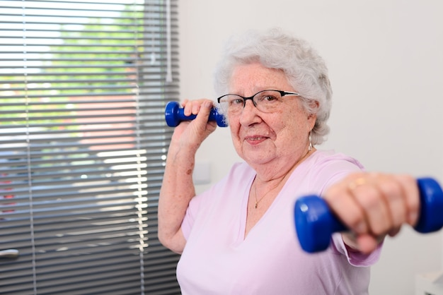 Portrait of an active and dynamic senior woman doing sport fitness at home