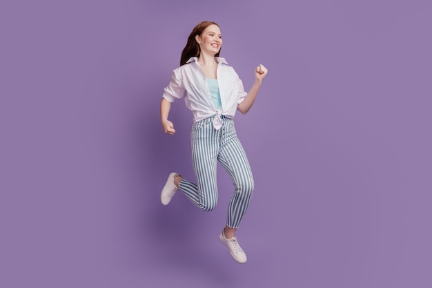 Portrait of active funny positive lady jump run on violet background