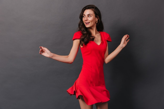 Portrait of active girl in red dress dancing with smile against black background. brunette in massive earrings has fun.