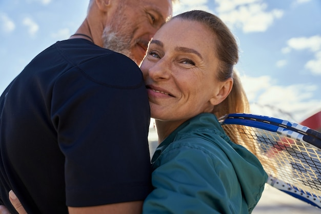 Portrait of active mature couple looking happy while embracing each other outdoors ready for
