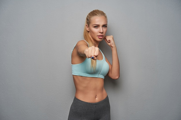 Portrait of active slim young woman with long blonde hair looking menacingly at camera and raising fists, being ready to fight, standing over light grey background in sporty clothes