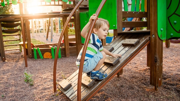Portrait of adorable 3 years old boy climbing on ladder on the children palyground at park