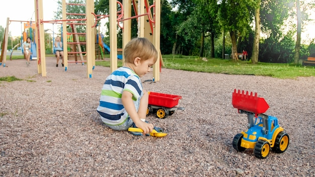 Portrait of adorable 3 years old toddler boy playing with toy truck with trailer on the playground at park